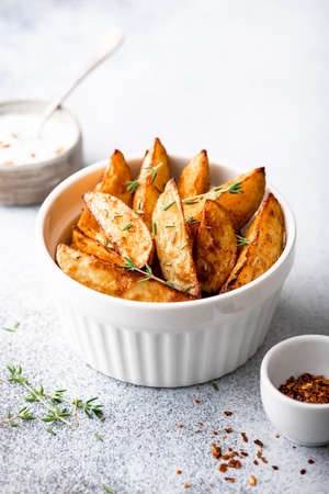 baked potato wedges with sauce and thyme on a light background
