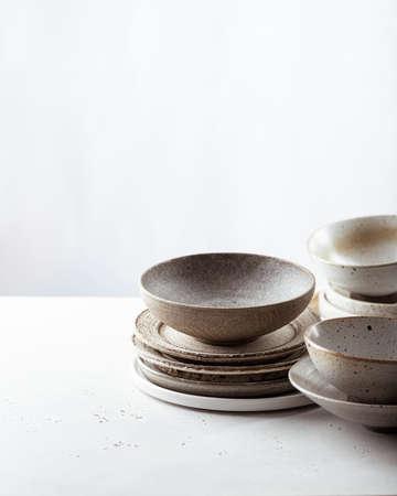 handicraft ceramics, empty craft ceramic bowl and plates on light background Reklamní fotografie