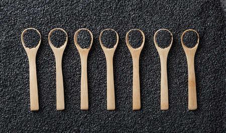 black sesame seeds in wooden spoons on a background of scattered sesame seeds