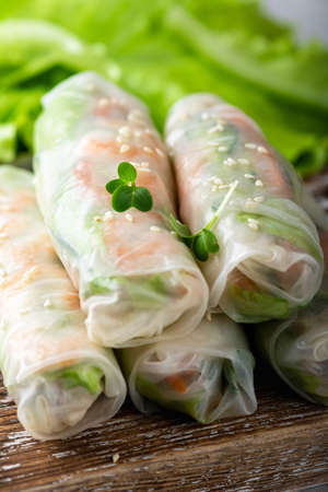 Traditional vietnamese spring rolls with shrimp, carrots, cucumber, green onions and rice noodles, selective focus