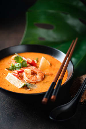 Tom Yam kung Spicy Thai soup with shrimp in a black bowl on a dark background, selective focus Reklamní fotografie