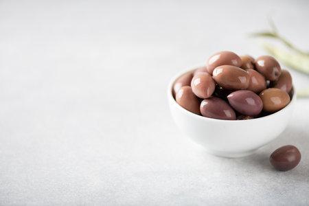 kalamata olives in white bowl on white background, copy space, selective focus Reklamní fotografie
