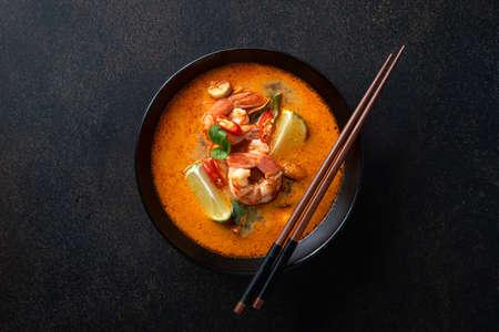Tom Yum soup with shrimp in a ceramic black bowl with chopsticks on a dark background, top view Reklamní fotografie