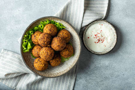 falafel balls in a ceramic bowl on a concrete background, top view