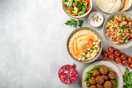 Middle eastern or arabic cuisines, falafel, hummus, tabouleh, pita and vegetables on a concrete background, view from above, copy space Reklamní fotografie
