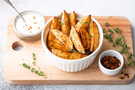 baked potato wedges with sauce on a light background