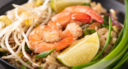 Pad Thai with shrimp on a stone background, selective focus, close-up