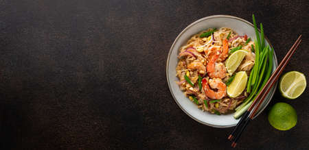 Pad Thai with shrimp in a ceramic bowl on a dark background, top view, copy space