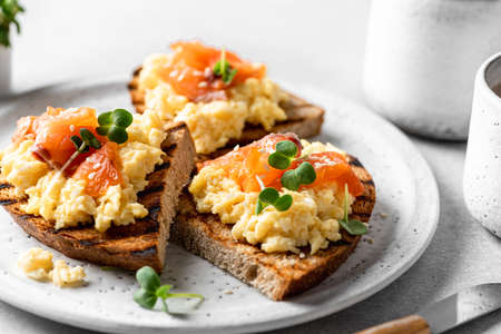 Scrambled egg sandwich with salmon on a ceramic plate on a white background, selective focus, close-up
