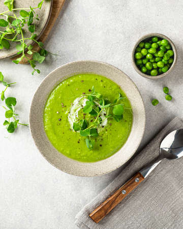 Green pea soup in a ceramic bowl, top view