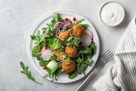 Falafel and fresh vegetables salad on a white ceramic plate on concrete background, top view. Reklamní fotografie