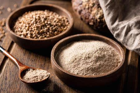 buckwheat and buckwheat flour on a wooden kitchen board, gluten-free. Reklamní fotografie