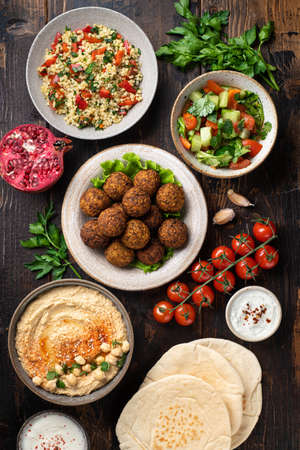 Middle eastern or arabic cuisines, falafel, hummus, tabouleh, pita and vegetables on wooden background, view from above