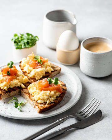 Scrambled egg sandwich with salmon on a ceramic plate on a white background, selective focus Reklamní fotografie