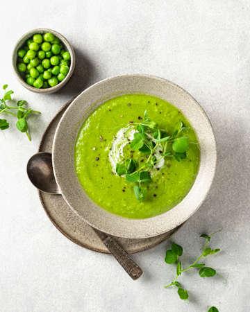 Green pea soup on gray concrete background, top view Reklamní fotografie