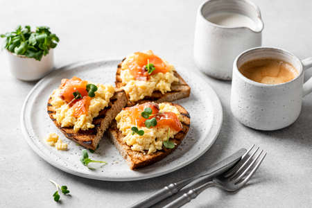 Scrambled egg sandwich with salmon on a ceramic plate on a white background, delicious and healthy breakfast, selective focus Reklamní fotografie