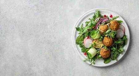Falafel and vegetables salad on a white ceramic plate on concrete background, copy space. Vegetarian food concept Reklamní fotografie