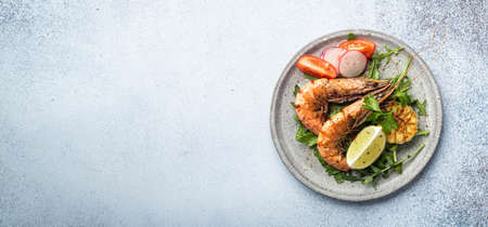 grilled tiger prawns with vegetables on a ceramic plate, top view, place for text