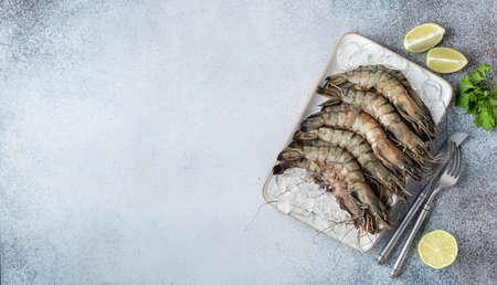 raw black tiger prawns on ice on a concrete background, top view, selective focus, copy space Reklamní fotografie