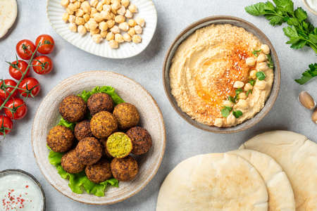 Chickpea dishes, falafel and hummus, on a concrete background, view from above, selective focus