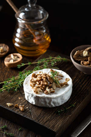 brie cheese with walnuts and honey on a wooden cutting board . Selective focus, dark background