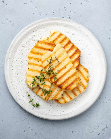 grilled halloumi cheese on a white ceramic plate, top view