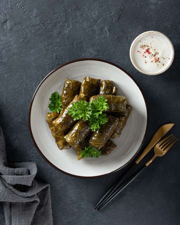 Dolma - stuffed grape leaves with rice and meat on a dark background, view from above. Traditional Greek. Caucasian and Turkish cuisine
