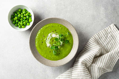 Green pea soup in a ceramic bowl on gray concrete background, top view