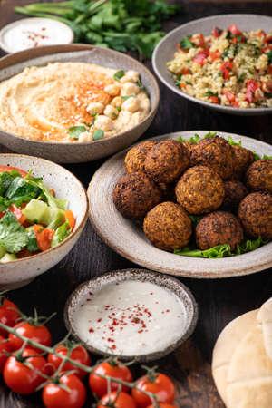 Middle eastern or arabic cuisines, falafel, hummus, tabouleh, pita and vegetables on wooden background, selective focus Reklamní fotografie