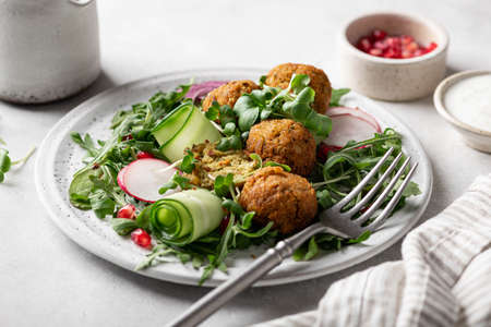 Falafel and fresh vegetables salad on a white ceramic plate on concrete background, selective focus.