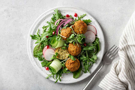 Falafel and fresh vegetables salad on a white ceramic plate on concrete background, view from above.