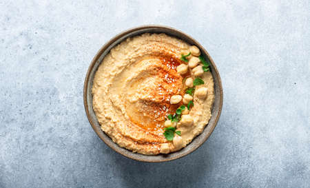 hummus in a ceramic bowl on a blue background, top view, copy space