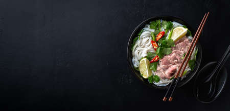 Pho Bo vietnamese soup with beef and rice noodles on a black background, top view, copy space Reklamní fotografie