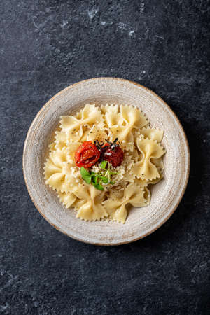 Farfalle pasta in a ceramic plate on a dark stone background, view from above