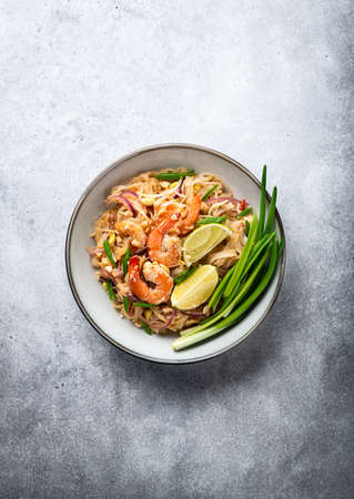 Pad Thai with shrimp on a concrete background, top view