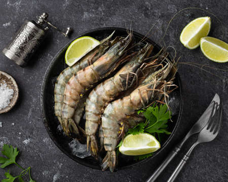 raw black tiger prawns on ice on a black background, top view, selective focus