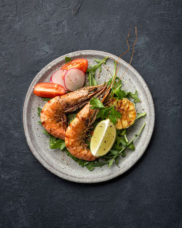 grilled tiger prawns with vegetables on a ceramic plate, top view Reklamní fotografie