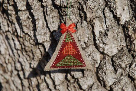 christmas tree ornament hanging on a rough bark Stock Photo