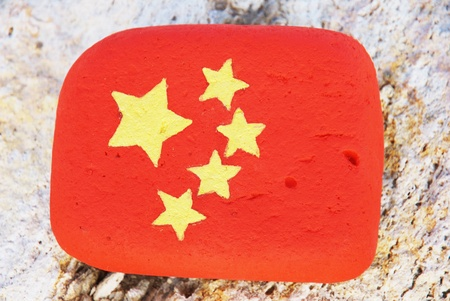 painted stone with the colouors of the chinese flag on the rock at the beach Stock Photo
