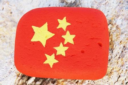 pierre peinte avec les colouors du drapeau chinois sur le rocher � la plage
