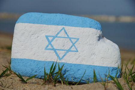Couleurs du drapeau d'Isra�l sur une pierre sur le sable Banque d'images