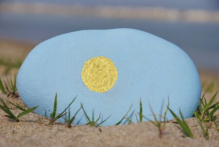 colours of the Palau flag on a stone over the sand
