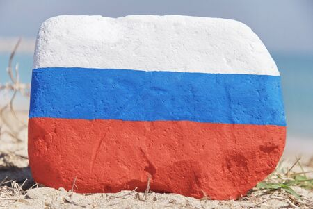 Russia flag painted over a stone over the sand Stock Photo