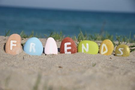mot amis sur des cailloux color�s sur le sable Banque d'images