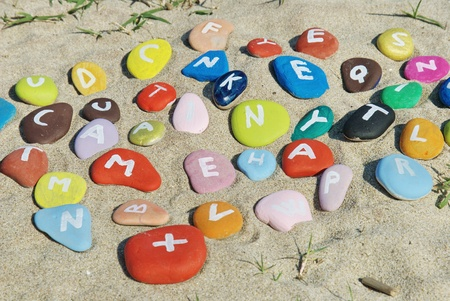 pebbles with colourful letters on the sand Stock Photo