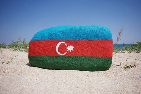 flag of Azerbaijan on a stone with sand background