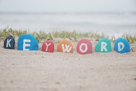 keyword on painted pebbles over the sand Stock Photo - 17041154