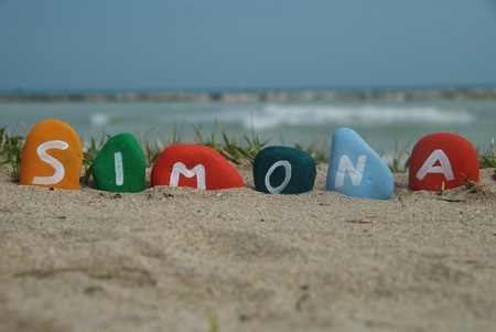 Simona, female name on colourful pebbles on the sand Stock Photo