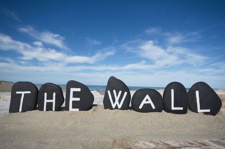The wall, conceptual black painted stones over the sand Stock Photo
