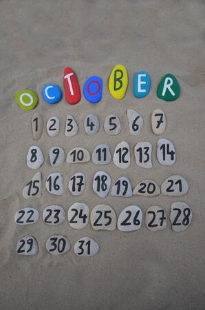 October calendar on stones with sand background